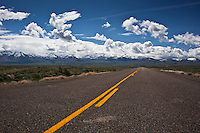 One of the two-lane roads that intersects with the interstate and heads off, straight and flat across Nevada's high desert toward the mountains on the horizion, maybe to climb into the clouds.