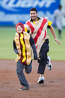 A young fan dressed as a hot dog races around the bases against a fan dressed as bacon between innings of the South Atlantic League game between the West Virginia Power and the Kannapolis Intimidators at CMC-Northeast Stadium on April 17, 2014 in Kannapolis, North Carolina.  The Power defeated the Intimidators 4-3.  (Brian Westerholt/Four Seam Images)