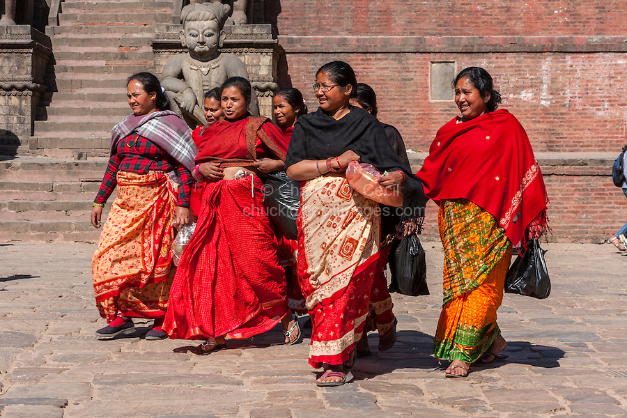 Bhaktapur, Nepal.  Women Walking through Taumadhi Tole Square.  Red and Black are the Colors Traditionally Worn by Bhaktapuri Women.