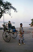 INDIA Calcutta Kolkatta, man-powered Rikshaw puller and passenge at river Hooghli made by idol maker at suburban Kumartuli / INDIEN Kalkutta, Rikscha am Fluss Hooghli
