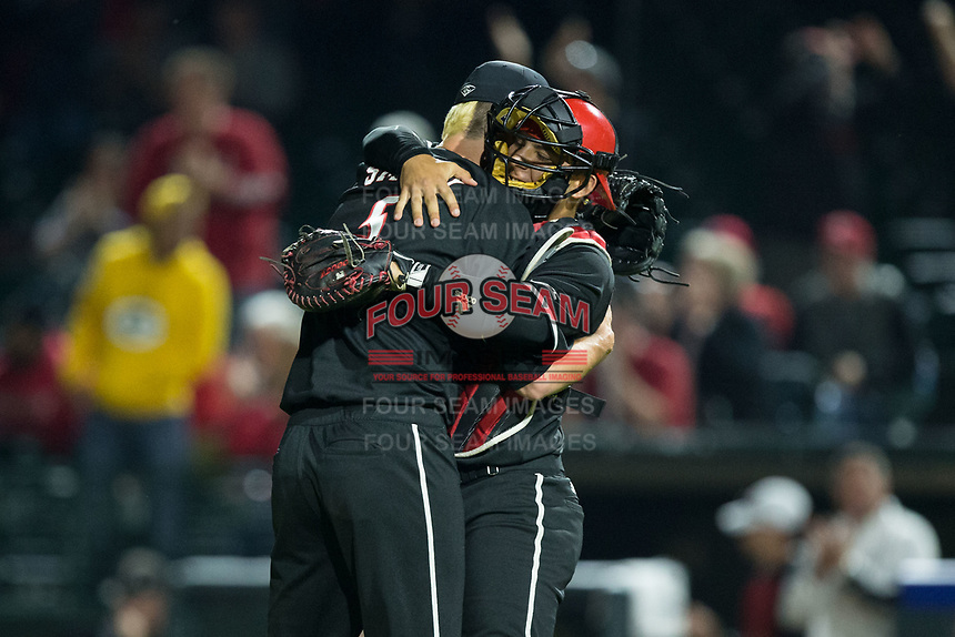 Louisville Cardinals relief pitcher Shay Smiddy (5) gets a hug from catcher Pat Rumoro (18) after closing out the win over the Notre Dame Fighting Irish in Game Eight of the 2017 ACC Baseball Championship at Louisville Slugger Field on May 25, 2017 in Louisville, Kentucky.  The Cardinals defeated the Fighting Irish 10-3.  (Brian Westerholt/Four Seam Images)