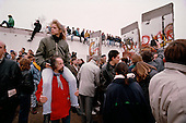 East Berlin, East Germany<br /> November 12, 1989<br /> <br /> A woman sits on the shoulders of a man to look at sections of the Berlin Wall that were removed. Germans gathered as the wall is dismantled and the East German government lifted travel and emigration restrictions to the West on November 9, 1989.