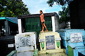 A young Filipino woman stands on the tombs and bathes in the rain at the Manila North Cemetery in Manila, Philippines. The scarcity of land and ever growing population has led the local filipinos to live in the same space around the graveyards in the Cemetary. Photo: Sanjit Das
