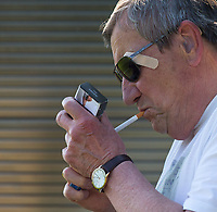Spectator lights a cigarette during the UHLSport Hellenic Premier League match between Flackwell Heath v Tuffley Rovers at Wilks Park, Flackwell Heath, England on 20 April 2019. Photo by Andy Rowland.
