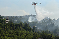 Pictured: A helicopter douses flames in Thrakomakedones near Athens, Greece. Saturday 07 August 2021<br /> Re: Forest fire in Varibobi, in the areas north of of Athens, Greece.