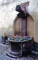 Riquewihr: Flower-filled old well on brick walk.