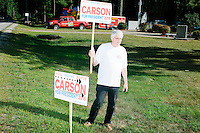 A campaign volunteer holds signs toward traffic for Republican presidential candidate Dr. Ben Carson at Londonderry Old Home Day in Londonderry, New Hampshire. Carson later showed up at the event to meet New Hampshire voters.
