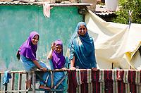 Smiling Muslim woman and children in colorful headscarves, Dal Lake, Srinagar, Kashmir, India.