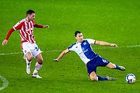 19th December 2020; Bet365 Stadium, Stoke, Staffordshire, England; English Football League Championship Football, Stoke City versus Blackburn Rovers; Stewart Downing of Blackburn Rovers slides for the ball on the wet grass as Thompson of Stoke closes in