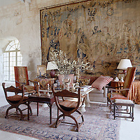 An arrangement of eclectic chairs is grouped under a vast 17th century Brussels tapestry that hangs across one of the stone walls in the entrance hall