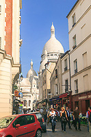 A busy street in Montmartre with the basilique du Sacré-Coeur in the background in Paris, France.