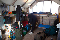 Volunteer John Riechart gets some gear from the volunteer sleep shack at the Cripple checkpoint 1/2 way into the race during the 2010 Iditarod