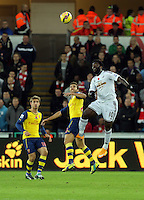 Sunday 09 November 2014 <br /> Pictured: Wilfried Bony of Swansea (R) heads the ball over Mathieu Flamini of Arsenal (C)<br /> Re: Barclays Premier League, Swansea City FC v Arsenal City at the Liberty Stadium, Swansea, Great Britain.