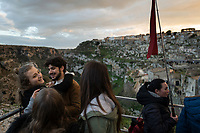 """Italy. Basilicata Region. Matera. At sunset, a group with their tour guide visit the historical centre. Known as la Città Sotterranea (""""the Underground City""""), Matera is one of the oldest continuously inhabited cities in the world, having been inhabited since the 10th millennium BC. Its historical centre """"Sassi"""", along with the Park of the Rupestrian Churches, was awarded World Heritage Site status by UNESCO since 1993. The Sassi di Matera are two districts (Sasso Caveoso and Sasso Barisano), well-known for their ancient cave dwellings.The Sassi originate from a prehistoric troglodyte settlement and are suspected to be among the first human settlements in Italy. There is evidence that people were living here as early as the year 7000 BC.The Sassi are houses dug into the calcarenite rock itself, which is characteristic of Basilicata, locally called """"tufo"""" although it is not volcanic tuff or tufa. The streets in some parts of the Sassi often run on top of other houses. The ancient town grew up on one slope of the ravine created by a river that is now a small stream. The ravine is known locally as """"la Gravina"""". In the 1950s, the government of Italy forcefully relocated most of the population of the Sassi to areas of the developing modern city. Until the late 1980s this was considered an area of poverty, since many of these houses were, and in some cases still are, uninhabitable. The current local administration, however, has become more tourism-oriented, and it has promoted the regeneration of the Sassi with the aid of the European Union, the government, UNESCO. Today there are many thriving businesses, pubs, restaurants and hotels. A tour guide or a tourist guide is a person who provides assistance, information on cultural, historical and contemporary heritage to people on organized tours and individual clients at Matera historical sites. On 17th October 2014, Matera was declared Italian host of European Capital of Culture for 2019. Basilicata is a region in Southern"""