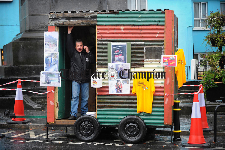 Michael Clancy of Clarecastle in his own representation of a South African shack, while fundraising in the Square, Ennis, for his next trip to South Africa on November 28th to help build homes for the poor. Photograph by John Kelly.
