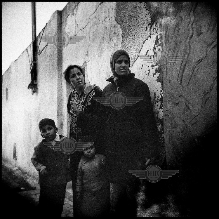 Tunisia/Tunis/March 2011.Two women with their children stands  in a narrow alley in Jabal al-Ahmar, a slum in Tunis, Tunisia..Giorgos Moutafis