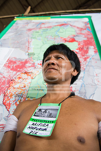 """Altamira, Brazil. """"Xingu Vivo Para Sempre"""" protest meeting about the proposed Belo Monte hydroeletric dam and other dams on the Xingu river and its tributaries. Cacique cheif Arifira Matipu and a map of the Xingu basin and participants badge."""