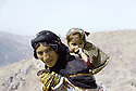 Irak 1985  Dans les zones libérées, région de Lolan, une femme sur la piste avec son enfant sur le dos  Iraq 1985 In liberated areas, Lolan district, a womn and her child on  the track