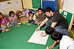 Education preschool 3-4 year olds young male teacher working with group of children at circle time making map of future activity trip to the pet store