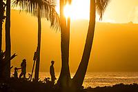 A family of three enjoy sunset at Hale'iwa Ali'i Beach Park, North Shore, O'ahu.