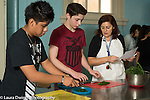 Education high school cooking elective taught by volunteers, female teacher working with male student on knife skills