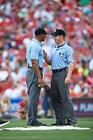 Umpires JJ January and Junior Valentine discuss a call during the All-Star Legends and Celebrity Softball Game on July 12, 2015 at Great American Ball Park in Cincinnati, Ohio.  (Mike Janes/Four Seam Images)