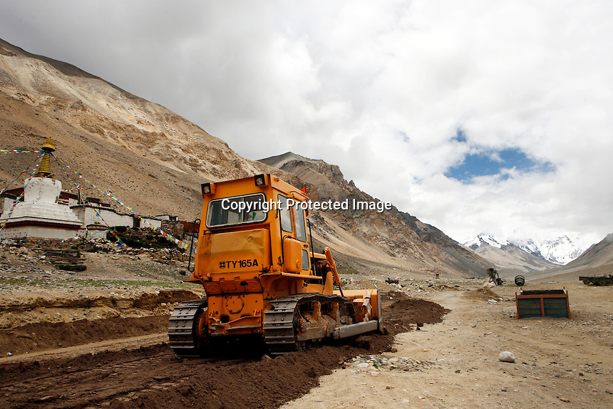 """China started building a controversial 67-mile """"paved highway fenced with undulating guardrails"""" to Mount Qomolangma, known in the west as Mount Everest, to help facilitate next year's Olympic Games torch relay./// A bulldozer in front of Rongbuk Monastery near Everest Base Camp.<br /> Tibet, China<br /> July, 2007"""