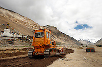 "China started building a controversial 67-mile ""paved highway fenced with undulating guardrails"" to Mount Qomolangma, known in the west as Mount Everest, to help facilitate next year's Olympic Games torch relay./// A bulldozer in front of Rongbuk Monastery near Everest Base Camp.<br /> Tibet, China<br /> July, 2007"