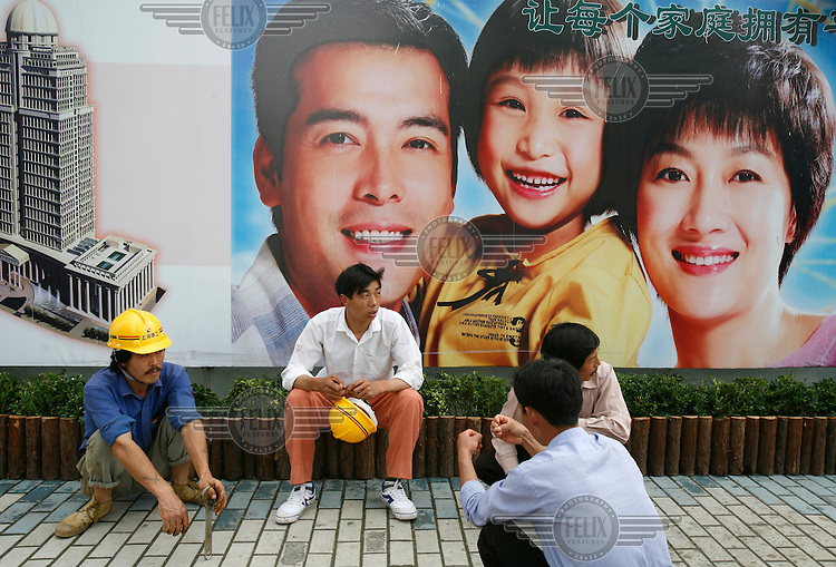 Construction workers sit in front of a billboard promoting China's one-child family policy...