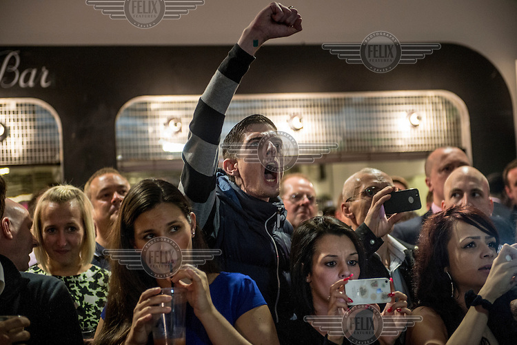 Spectators watch and cheer at a white collar boxing event at the London Irish Centre where the 'Carpe Diem' boxing event is taking place. <br /> <br /> 'White-collar boxing' is a growing phenomenon amongst well paid office workers and professionals and has seen particular growth in financial centres like London, Hong Kong and Shanghai. It started at a blue-collar gym in Brooklyn in 1988 with a bout between an attorney and an academic and has since spread all over the world. The sport is not regulated by any professional body in the United Kingdom and is therefore potentially dangerous, as was proven by the death of a 32-year-old white-collar boxer at an event in Nottingham in June 2014. The London Irish Centre, amongst other venues, hosts a regular bout called 'Carpe Diem'. At most bouts participants fight to win. Once boxers have completed a few bouts they can participate in 'title fights' where they compete for a replica 'belt'.