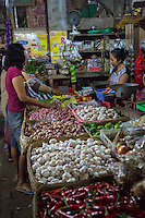 Bali, Indonesia.  Early-morning Shoppers Looking at Peppers, Garlic, Onions, Limes.  Jimbaran Market.