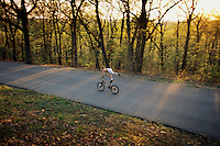 A young, daredevil bicyclist rides down a carriage road that is closed to vehicular traffic in Iroquois Park. Frederick Law Olmsted created pathways for strollers and curving roads for carriages, but might not have ever have imagined this use. <br /> <br /> Three parks in Louisville are named to honor a tribe--Cherokee, Shawnee and Iroquois--that once had shared the dark and bloody hunting grounds of Old Kentucky.