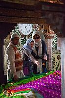 Fatehpur Sikri, Uttar Pradesh, India.  Inside the Mausoleum of Sheikh Salim Chishti.  Women Tossing Rose Patals on the Grave.