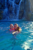 Two smiling young girls play happily in a freshwater pool with a cascading waterfall behind them.