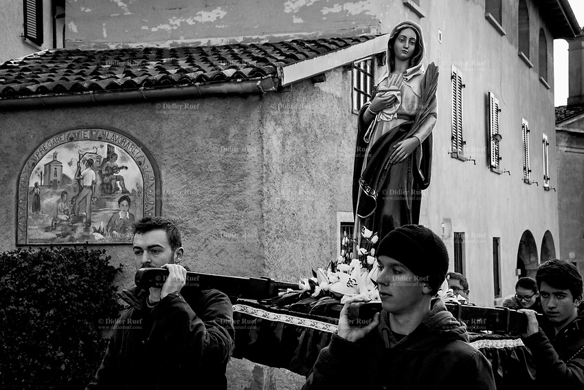 """Switzerland. Canton Ticino. Cadro. Religious procession. Four young men carry a wooden sculpture of The Virgin Mary during the """"Festa patronale di Sant'Agata"""". A mural painting on a private house's wall with the words Pray ( Pregare) and Work ( Lavorare), and various drawings with a church in the countryside, a musician and farmers at work in the fields. Mary was a 1st-century BC Galilean Jewish woman of Nazareth, and the mother of Jesus, according to the New Testament. Christians believe that she conceived her son while a virgin by the Holy Spirit. The Gospel of Luke begins its account of Mary's life with the Annunciation, when the angel Gabriel appeared to Mary and announced her divine selection to be the mother of Jesus. The Catholic Church holds distinctive Marian dogmas, namely her status as the Mother of God, her Immaculate Conception, her perpetual virginity, and her Assumption into heaven. Cadro is quarter of the city of Lugano and a former municipality in the district of Lugano. 4.02.2018 © 2018 Didier Ruef<br /> <br /> ."""