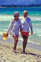 Senior couple walking down Kailua beach, Oahu