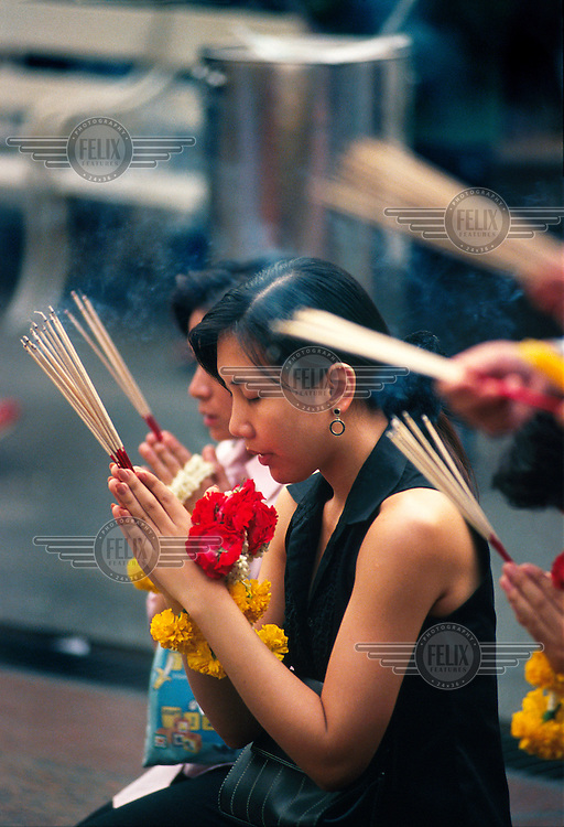 Women praying and burning incense in the Erawan shrine. This is a shrine to Brahma, the ancient Hindu god of creation, and Erawan, his elephant. It is located in one of the busiest corners of modern Bangkok, in the shadow of the Grand Hyatt Erawan Hotel - whose existence is the reason for the shrine.