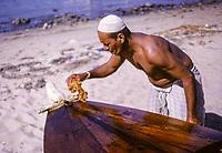Kuwait November 1966.  Kuwaiti Oiling his Boat to Preserve the Wood.