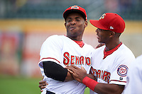 Harrisburg Senators Isaac Ballou (left) and Rafael Bautista (right) joke around during warmups before a game against the New Hampshire Fisher Cats on June 2, 2016 at FNB Field in Harrisburg, Pennsylvania.  New Hampshire defeated Harrisburg 2-1.  (Mike Janes/Four Seam Images)