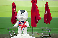 China. Shanghai. World Expo. Expo 2010 Shanghai China. A smiling chinese white dummy, wearing the Union Jack,  stands on a plastic table. Red umbrellas and green walls. The United Kingdom of Great Britain and Northern Ireland uses as its national flag the royal banner known as the Union Flag or, popularly, Union Jack. The current design of the Union Flag dates from the union of Ireland and Great Britain in 1801. It consists of the red cross of Saint George (patron saint of England), edged in white, superimposed on the Cross of St Patrick (patron saint of Ireland), which are superimposed on the Saltire of Saint Andrew (patron saint of Scotland). 25.06.10 © 2010 Didier Ruef.