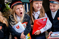 Estonia, Tallinn, Old town, UNESCO World Heritage Site. Children in uniforms bring flowers to their teachers for the first day of school,