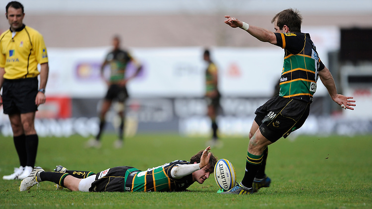 Lee Dickson of Northampton Saints (left) steadies the ball in the wind as Stephen Myler takes a penalty kick during the Aviva Premiership match between London Welsh and Northampton Saints at the Kassam Stadium on Sunday 14th April 2013 (Photo by Rob Munro)