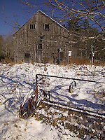 Farm tools covered with snow with barn in background&#xA;<br />