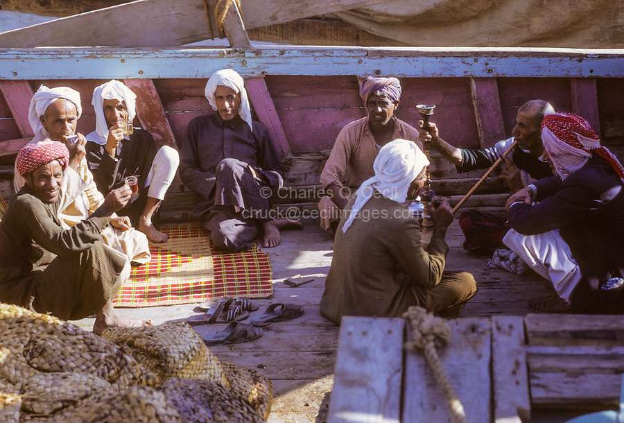 Dubai 1972, United Arab Emirates.  Dhow Crewmen Relaxing while Tied up alongside The Creek.