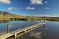 Man photographing from pier at Summer Lake wildlife Refuge, Oregon