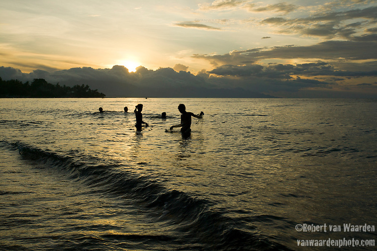 Young boys work with a fishing net on the north coast of Bali near Anturan, Indonesia.