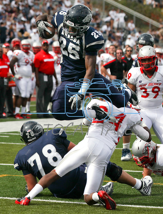 Nevada's Stefphon Jefferson hurdles over New Mexico defender Destry Berry during the first quarter of an NCAA college football game in Reno, Nev., on Saturday, Oct. 15, 2011. (AP Photo/Cathleen Allison)