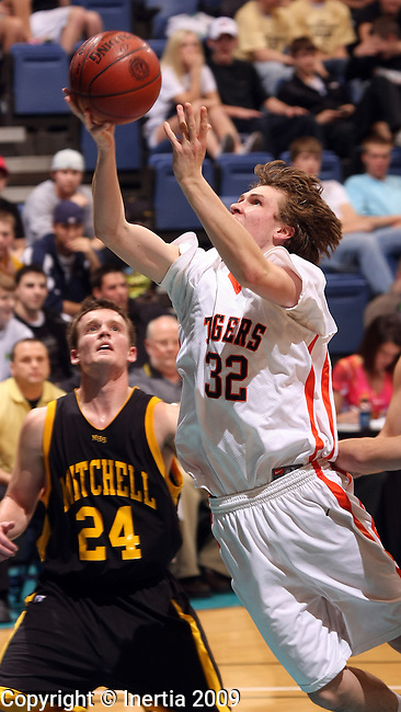 SIOUX FALLS, SD - MARCH 19:  Riley Hoistad #32 of Huron lays the ball up past Bretton Young #24 of Mitchell in the first half of their quarterfinal round game at the 2009 Class AA Basketball Championships Thursday night at the Sioux Falls Arena.  (Photo by Dave Eggen/Inertia)