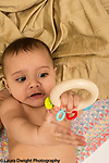 Infant boy age 6 months closeup holding toy transferring it hand to hand