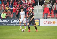 Toronto, Ontario - May 3, 2014: Toronto FC midfielder Michael Bradley #4 and New England Revolution forward Patrick Mullins #7 in action during a game between the New England Revolution and Toronto FC at BMO Field.<br /> The New England Revolution won 2-1.